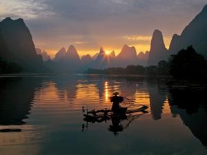 Fishermen and osprey in Li River Guilin